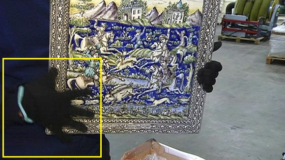 'A Customs officer showing one of the seized artworks. The 15th century Ottoman period piece was looted from a shrine in Syria.' (c) Yle Uutiset, 5th June 2015