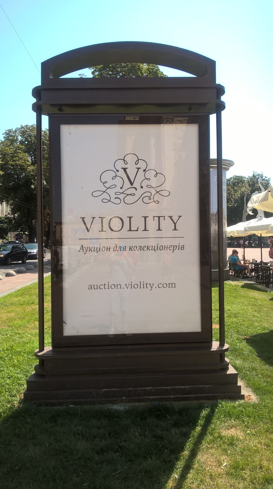 an advert for online auction site Violity, on a scrolling baord in front of a museum in a city centre square, Lviv, Ukraine